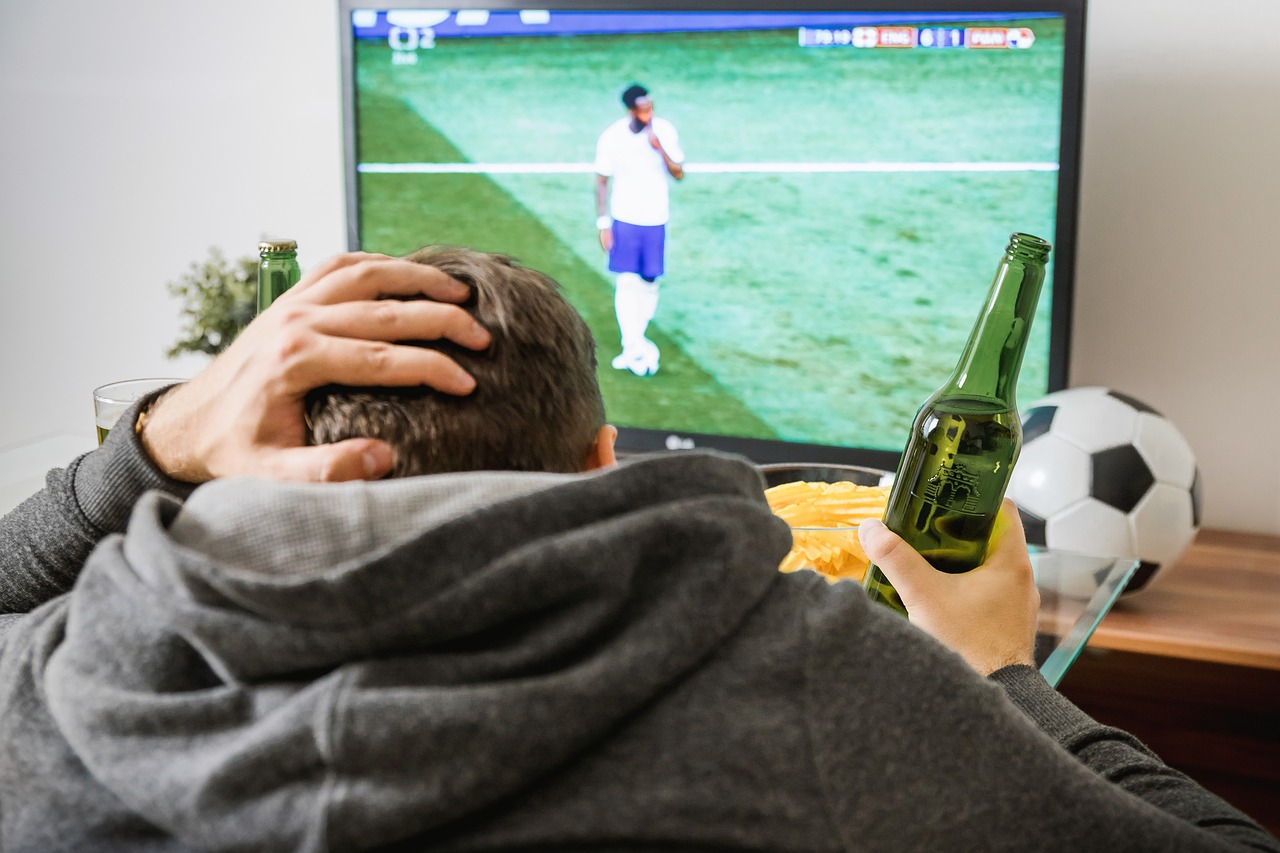 man watching football game on tv